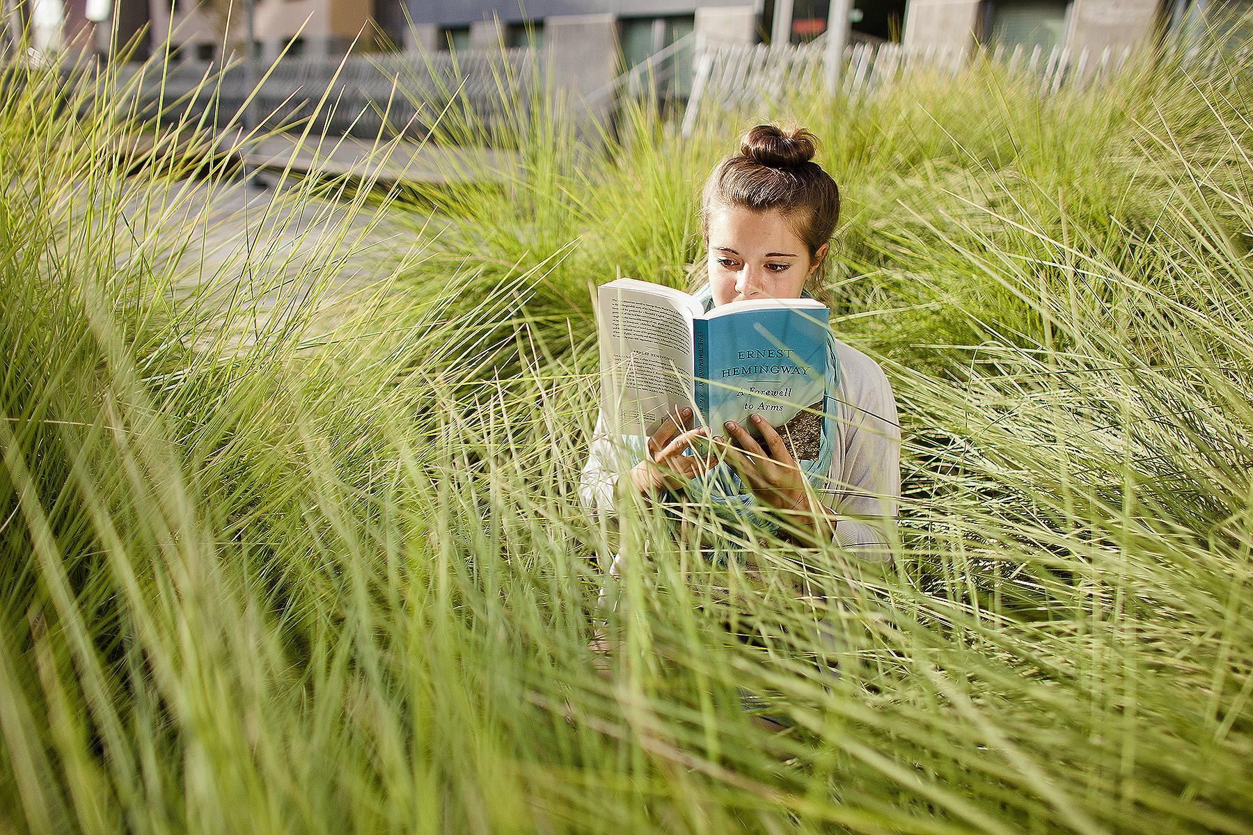 UC Berkeley student reading Hemingway in the grass