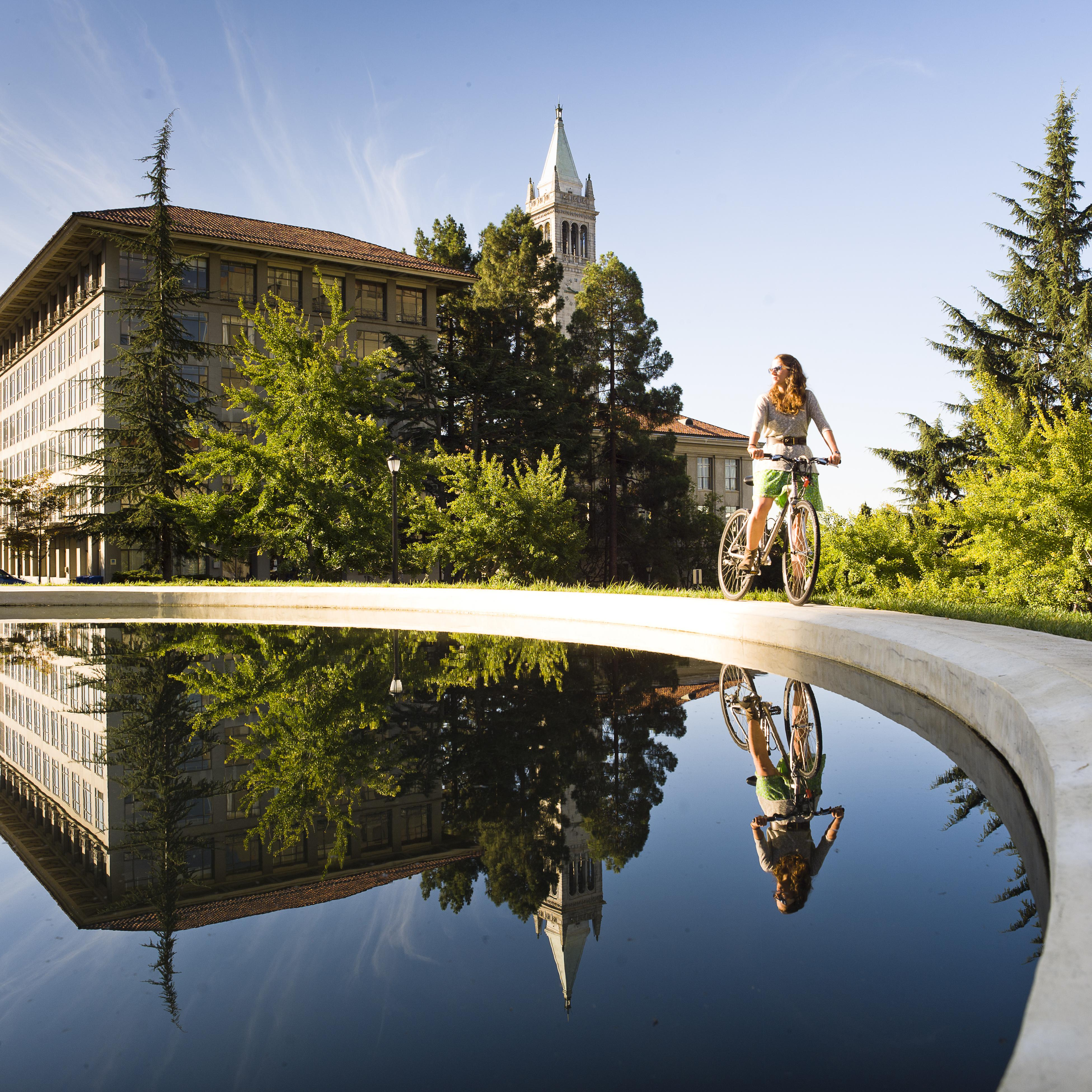 student riding bicycle near reflecting pool on UC Berkeley campus