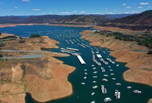 Houseboats in Lake Oroville are dwarfed by the exposed banks.