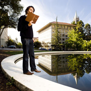 student reading a book on the edge of the Hearst Mining reflection pool