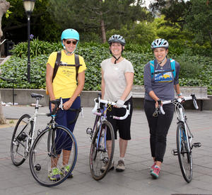 group of 3 employees pose on bike to work day