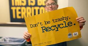 "student holding pro-recycling sign saying, ""Don't Be Trashy."""