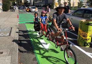 man and child riding bikes in bike lane